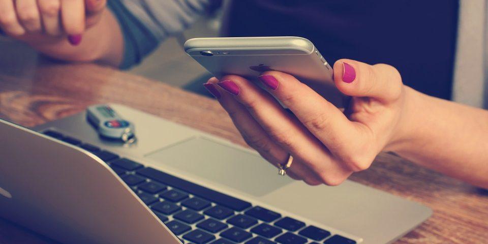 Kvinde med smartphone og bærbar computer